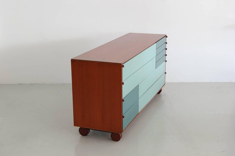 Walnut wrapped chest of drawers by B&B Italia. Drawers are geometric patterns of green-blues with leather tab pulls. Piece is an incredible find and a versatile piece.