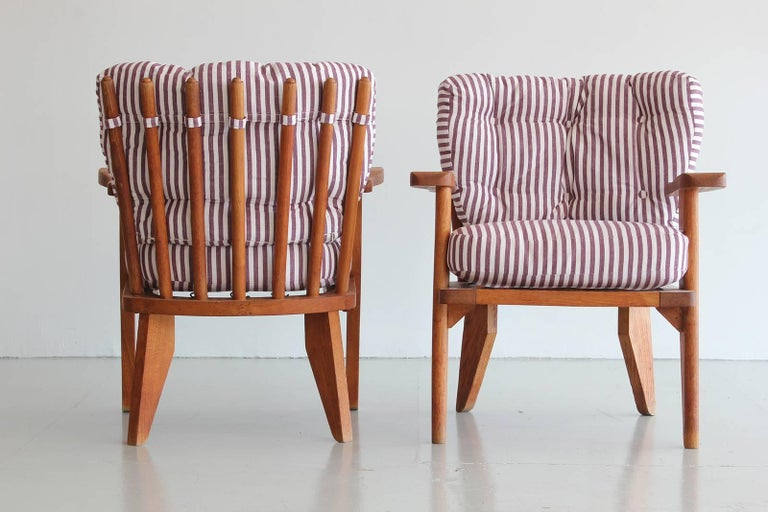 Guillerme & Chambron pair of chairs in oak with floating arms and spindle backs.