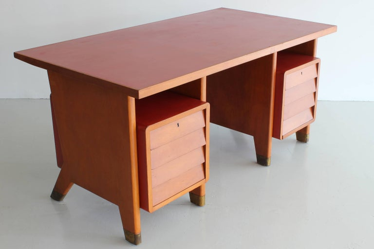 Gio Ponti designed desk for city offices of Forli, Italy. Original red linoleum writing surface with same linoleum wrapping the floating drawers. Brass sabots on the signature Gio Ponti leg.