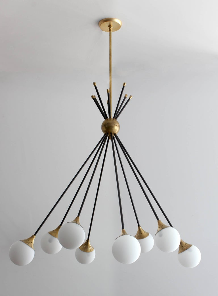 Exceptional Italian chandelier with signature Stilnovo opaline glass globe bulbs and spring clasps in a dramatic drop down direction.