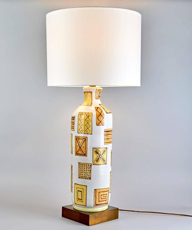 A graphically stunning ceramic table lamp by postwar Italy's greatest ceramist, Guido Gambone. The enigmatic design of intricately but spontaneously decorated squares and rectangles is arrayed over the surface of the ceramic lamp-base with the