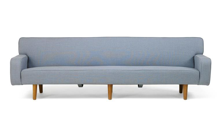 This substantial Hans Wegner sofa brings together all of the virtues of Danish design in its reconciliation of sleekness with restraint, and of jet-set modernity with the tradition of workmanship. This is the rare 99-inch-long variant of Wegner's