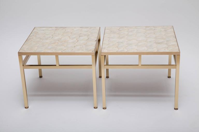 As elegant in a town house as a beach side cottage. Professionally restored pair of side tables have brushed, solid brass frames with inlaid tops of pearlescent, creamy white capiz shell. Attributed to William