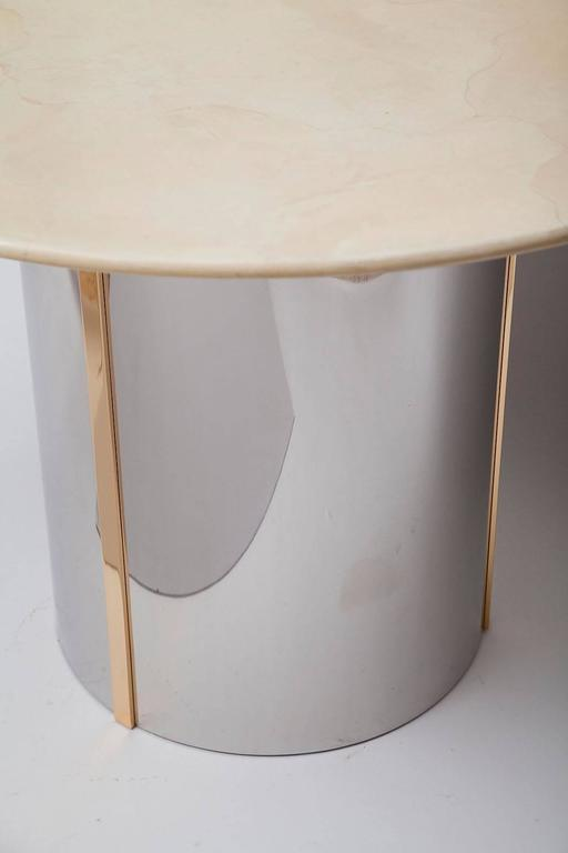 Finely-crafted center table in the style of Karl Springer has a polished steel and brass base with pale goatskin top. Circa 1975.