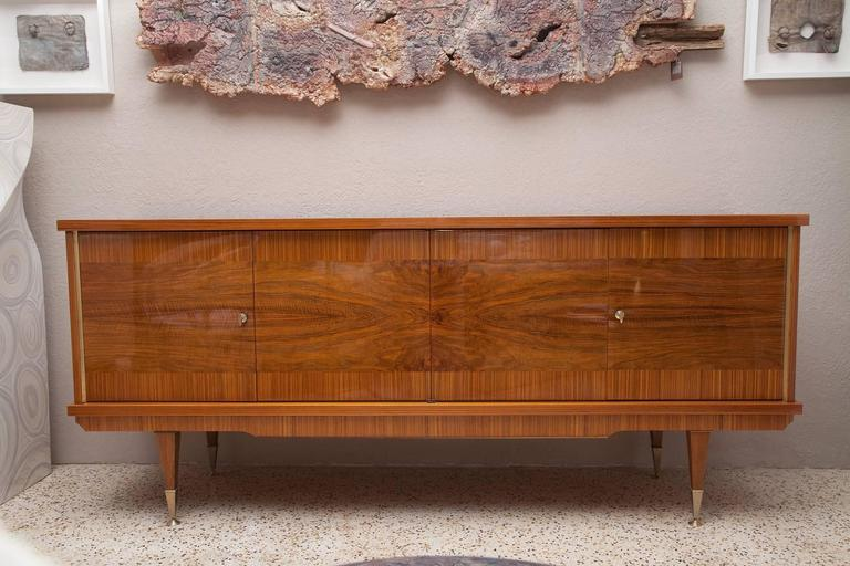 Dramatic 1960s French credenza in lacquered Zebra wood and burl walnut veneers. Sycamore interior with two wood shelves and one smoked glass shelf. Original, but un-wired interior light and original bronze-finished details and keys.