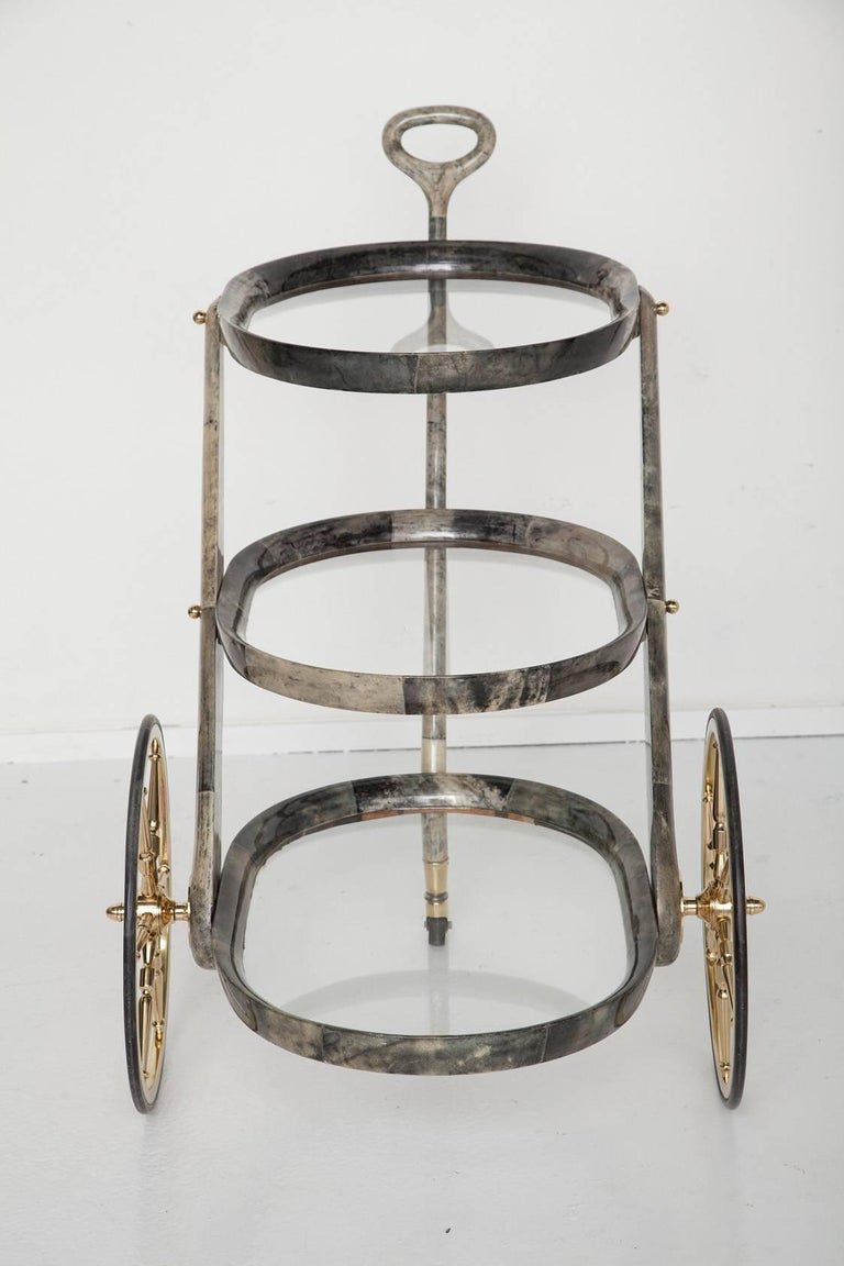 Gorgeous lacquered goatskin bar cart by Aldo Tura, circa 1950. Varying intensities of marbled grey and cream goatskin, with solid brass hardware, professionally polished with coated with protective lacquer finish.