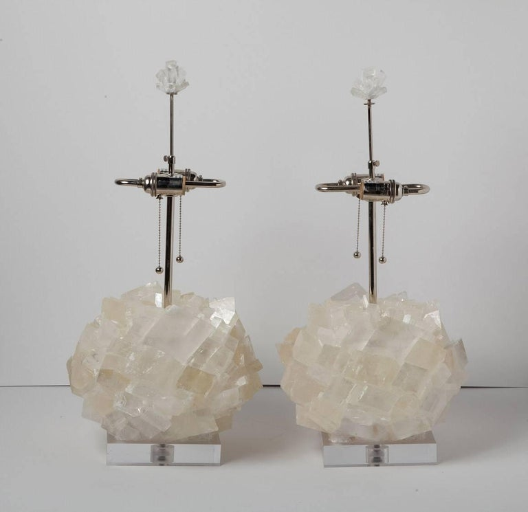 Glamorous pair of natural crystal table lamps by Kathryn McCoy in prismatic optical calcite on acrylic bases. Fabric cord and nickel hardware, with matching crystal finials. (Shades not included).