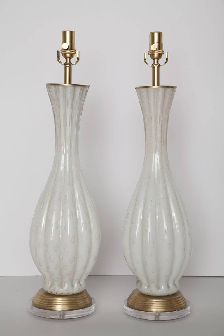 1960s handblown Murano table lamps in ribbed white glass with controlled bubbles and gold leaf. We've added a one inch acrylic base to the fully restored brushed brass hardware, and re-wired with new sockets and white fabric cord. 27 inches to top