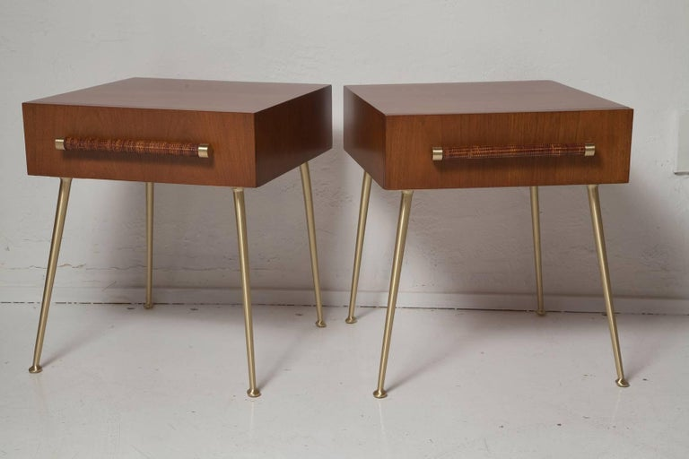 Designed by T.H. Robsjohn-Gibbings for Widdicomb Furniture Company, this rare pair of fully restored 1950s American walnut nightstands have cane wrapped handles and brushed brass legs and fittings. Fabric labels in both. Model no. 4001.