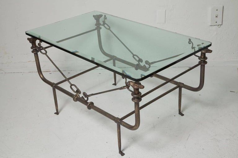 Unique Giacometti-style iron coffee table in patinated bronze finish with 0.5 in. beveled glass top supported by whimsical foxes at each of its corners, circa 1970.