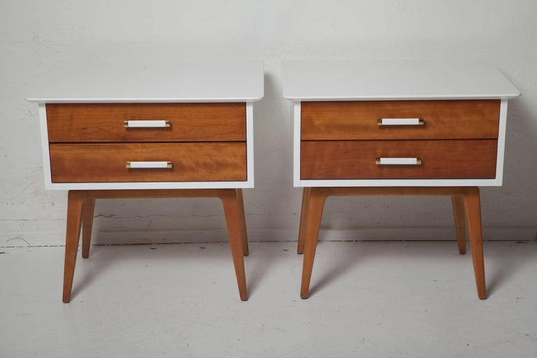 Fresh, fully restored pair of nightstands by Renzo Rutili have white lacquered bodies with contrasting cherrywood drawer fronts, legs, and handles with polished brass trim, circa 1955.