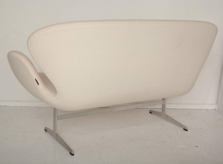 Hand-stitched upholstery in a creamy wool blend fabric follows the sinuous lines of this iconic Swan settee, designed in 1958 by Arne Jacobsen for the SAS Royal Hotel in Copenhagen. This example was produced in the 1990s by Fritz Hansen.