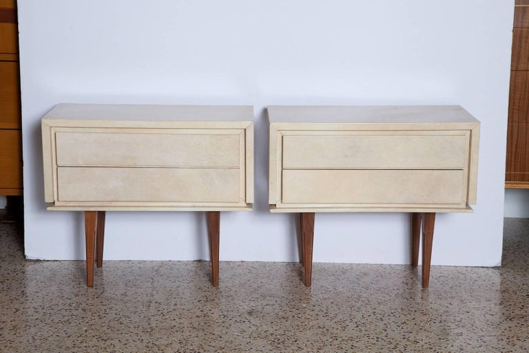 Diminutive pair of 1960s French parchment covered nightstands in subtle shades of cream and palest grey atop simply carved solid mahogany legs.