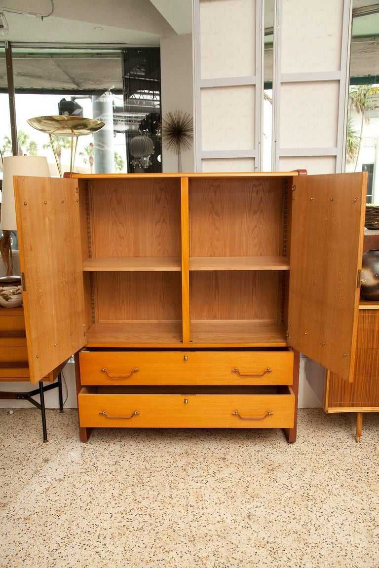 A large Jacques Adnet cherry cabinet with oak interior, cast brass hardware, and leather covered steel legs and trim, France circa 1950.