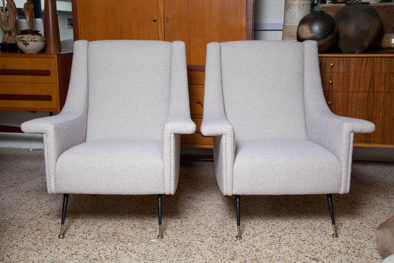 Large and comfy 1950s Italian lounge chairs, fully restored and upholstered in a soft, thick alpaca, wool, and silk blend in pale, pearly, greige. Black enameled legs with polished brass sabots.