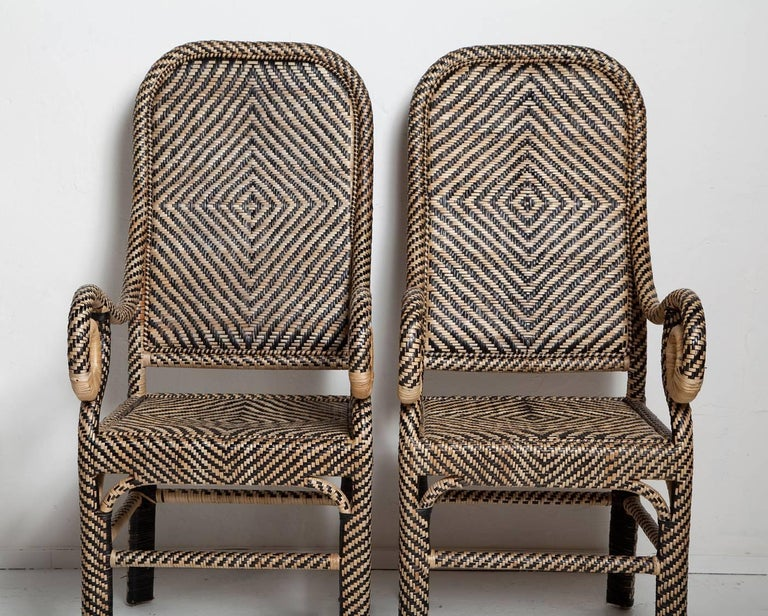 Graphic patterns, natural materials and pleasing design go into this arresting pair of rattan armchairs, handwoven in the Philippines, circa 1980. Very good condition. Sturdy with no losses or breaks to the rattan.