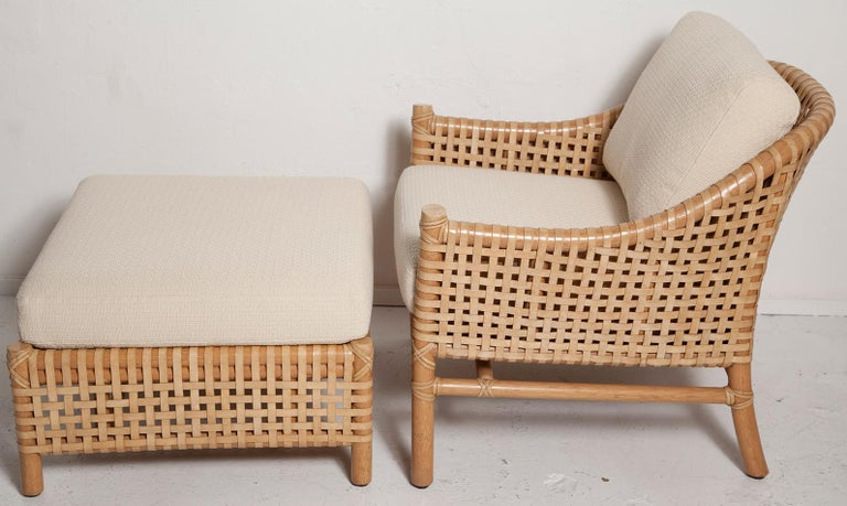 An eye-catching vintage lounge chair and ottoman set by McGuire made entirely of rawhide leather straps woven onto a thick bamboo frame. Near mint condition with new textured cotton upholstery. This circa 1980 set retains its original brass McGuire
