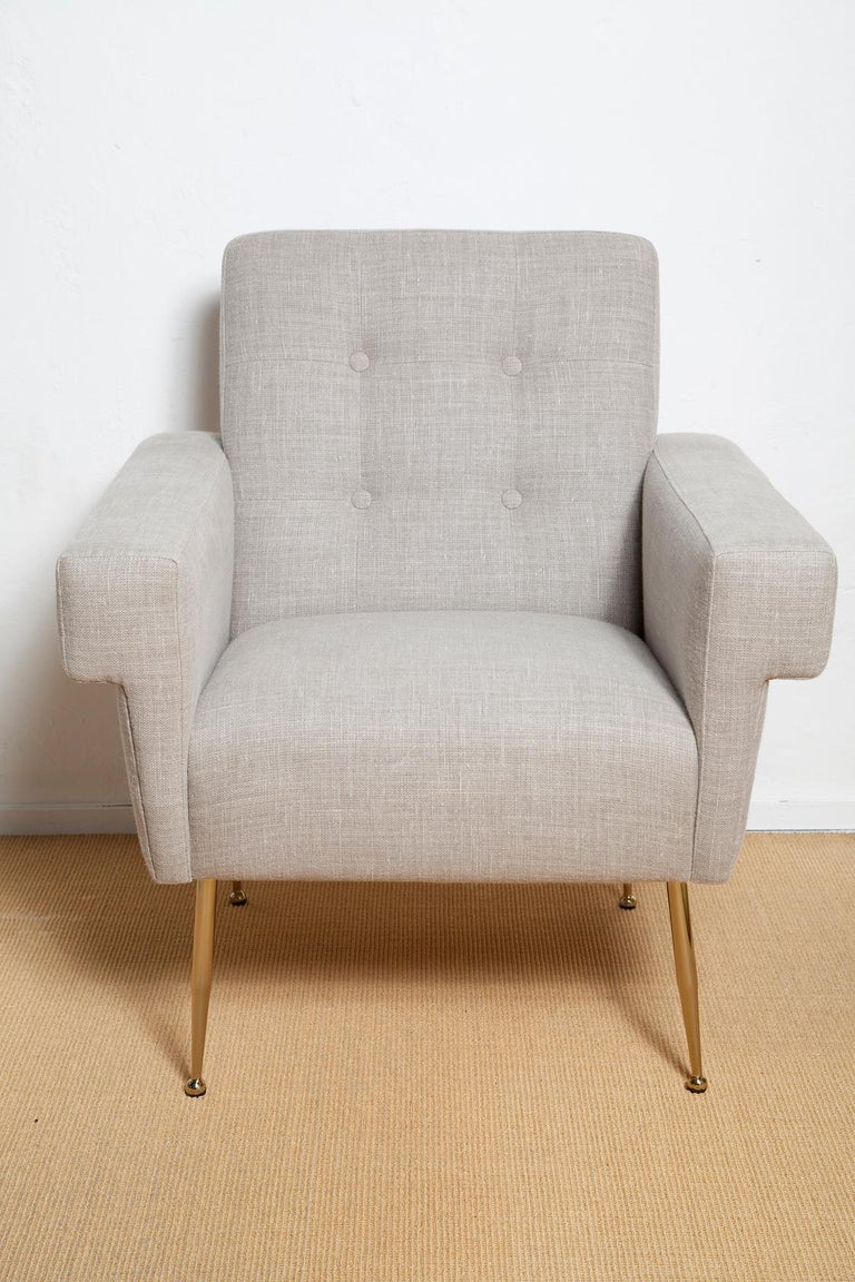 Inspired by a 1950s Italian original, our bench-made Milano lounge chair features bold square arms and clean masculine lines evocative of the stylish, no-nonsense city it was named after. This pair features brass legs and a thick, washed Belgian