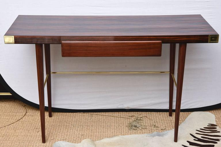 This sleek and fully restored Mid-Century Modern Walter Charak labeled desk/writing desk for Tommi Parzinger is exquisite. The 4 polished brass corner tabs and brass stretcher on the bottom compliment the beautiful woods of Macassar ebony on the