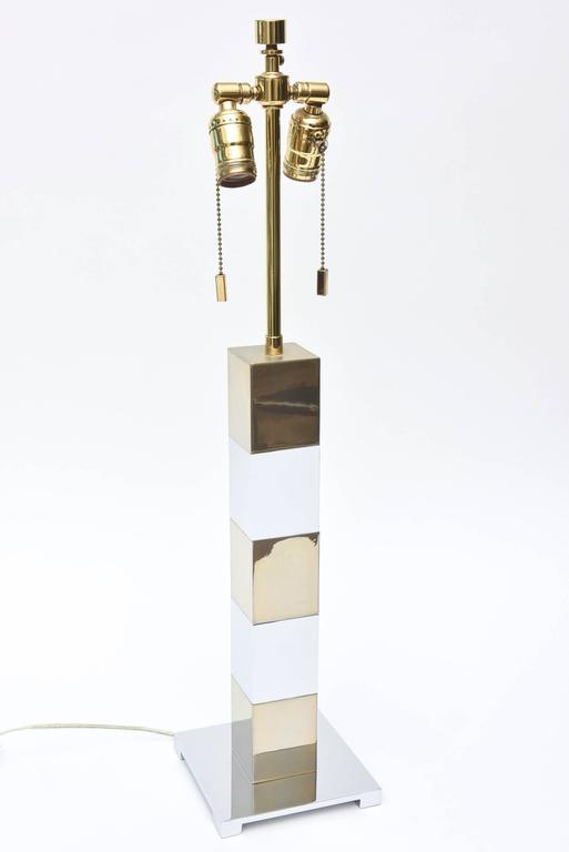 "This modern table or desk lamp is in the style of Karl Springer. It has alternating chrome and brass cubes that sits on a chrome base. There are two pull chains for the double socket with the original finial. It is 22.5"" H to the bulb socket. It has"