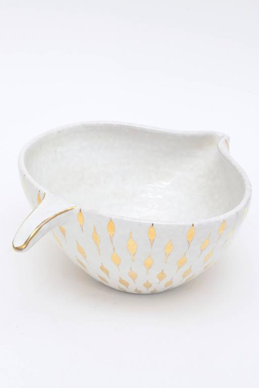 This sculptural vintage Italian Aldo Londi for Bitossi ceramic bowl or vessel has gold painted teardrop like surround shapes on the exterior over white ceramic with a short sculptural handle. It is called the feather plume. The shape is organic with