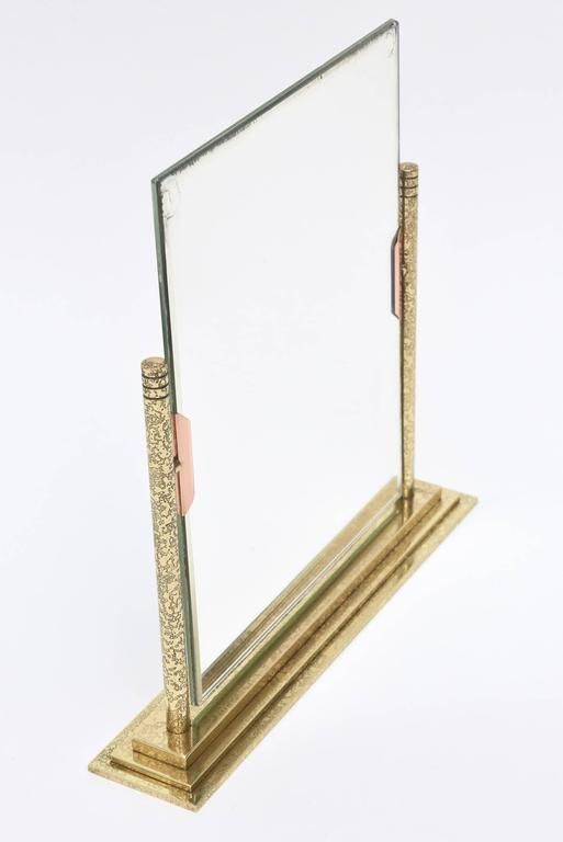 The hand tooled brass on the bottom and frame is a tight beautiful design. The rose colored tabs on the front are bronze. It is a both a picture frame on one side and a mirror on the other. The metal has all been professionally polished.  Please