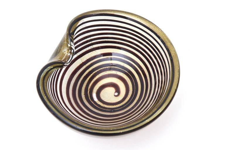 This stunning vintage Italian Murano Seguso spiral designed glass bowl has the spiral technique of layered concentric circles filled with gold aventurine. It is of the technique of Zebratti. It is eggplant to aubergine brown. This is a great bowl as