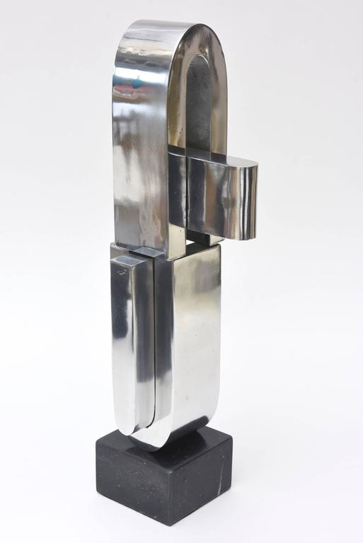 This fabulous double U-shaped abstract sculpture by the noted artist Mary Preminger is so modernist. It transcends time. It is chrome on a black marble original base. It was executed in 1968. It is unsigned though but definitely her work. It is