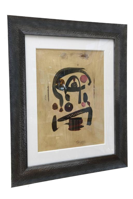 This wonderful abstract vintage painting has influences of Miro and his painterly strokes and gestures of paint in abstract form. The background is tan with stokes of black dark gray and elements of subdued red. It also has influences to the Art