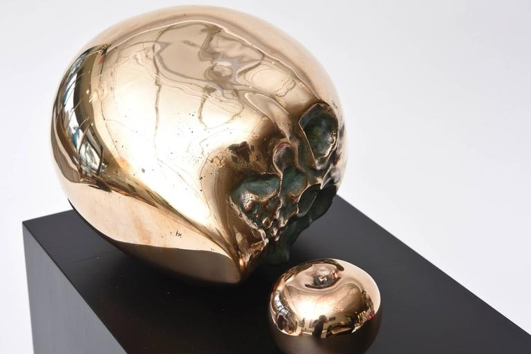 This wonderful vintage bronze sculpture is dimensional and large. The polished bronze large skull head and small apple are yin and yang. It sits on an ebonized wood original base that has been redone. It is signed inside by an unknown sculptor named