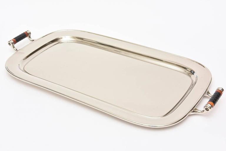 This very versatile two handled vintage Art Deco rectangular nickel silver over chrome and aluminum bar or serving tray is so handsome. It is marked on the back Manning Bowman & Co. Meriden, Conn. The original Bakelite wrapped handles are amazing.