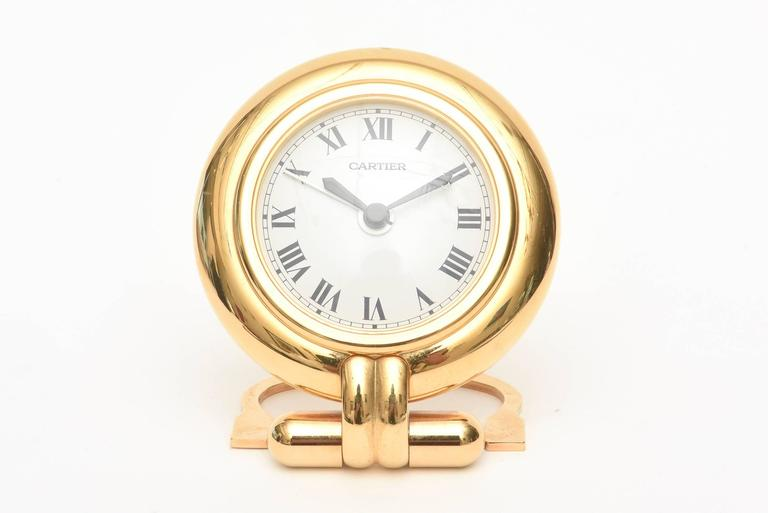 This stunning and elegant vintage Cartier quartz desk, travel or nightstand small fold up Roman numeral clock has its original box, certificate and papers. It is called the Colisee Clock collection and is 24 karat gold plated. It folds up for