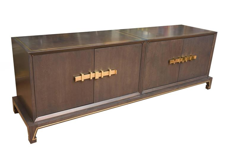 This magnificent and fully restored original Tommi Parzinger Mid-Century Modern low cabinet is sculptural with its monumental polished solid brass hardware that opens the cabinet doors on both sides. It has brass inlay on the top and bottom and