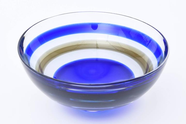 This stunning and vibrant cobalt blue and sage brown striped banded glass Swedish Orrefors vintage crystal glass bowl has the original sticker on it from the time of the 1960s. This is a beauty. There is one brown sage stripe admits the cobalt