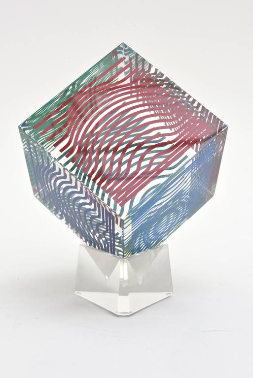 This four sided every changing graphic optical Op Art lucite vintage cube sculpture by Victor Vasarely is vintage from the 1970s. They were produced in a large edition at the time but not numbered. It is a silkscreen acrylic. It is not signed but
