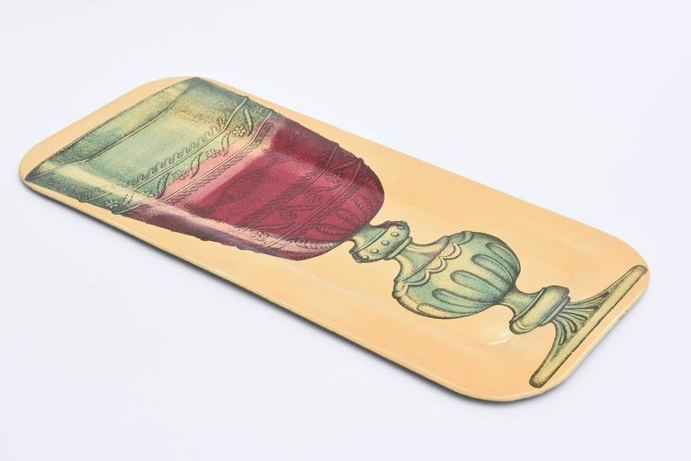 This great and rare serigraphed Italian Mid-Century Modern metal serving tray is the work of Italian artist, dreamer and genius Piero Fornasetti. This is great for barware. This particular image of this rectangle tray is rarer. It is from the 1950s.