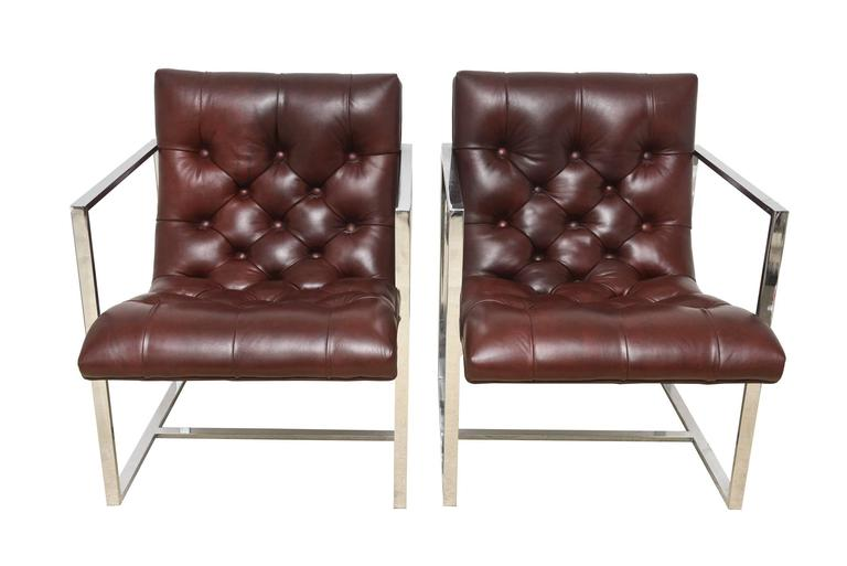 These gorgeous pair of Milo Baughman architectural side chairs/lounge chairs are a chrome frame with fine leather tufted seats in a brownish burgundy color. They have buttons of leather as part of the tufting. Their form is of a scoop nature. They