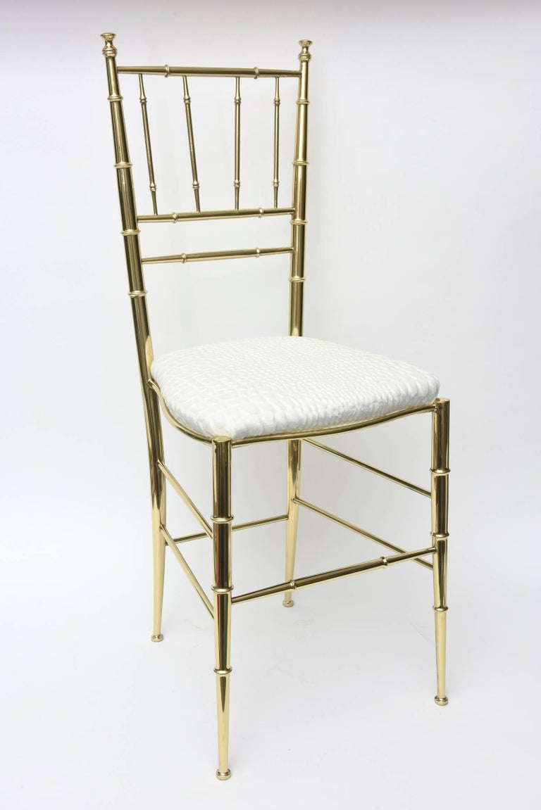 This lovely polished brass Italian midcentury Chiavari side chair has faux bamboo elements. It has been just re-upholstered in a stunning textural cut velvet crocodile white to off-white upholstery. Tres Chic! The brass has been professionally