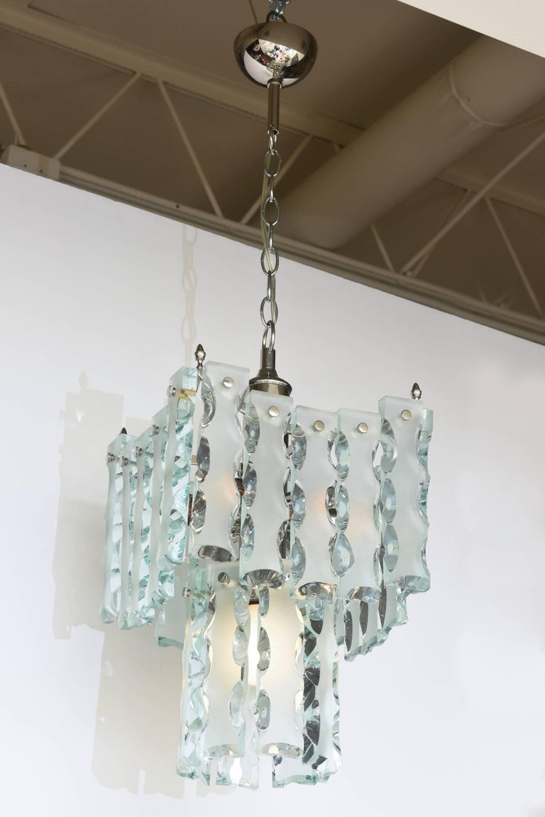 This Mid-Century Modern Italian two-tiered pendant glass and buckle silver caged chandelier has been attributed to Fontana Arte. It has a beautiful elegance to it. The cage has all been re-restored with nickel silver over the original brass cage. It