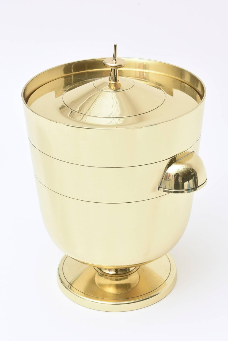 This Classic modernist Mid-Century Modern and solid brass hallmarked Tommi Parzinger for Dorlyn ice bucket and or champagne cooler is always timeless with its form and lines. It has the original mercury silver glass liner. This is great barware and