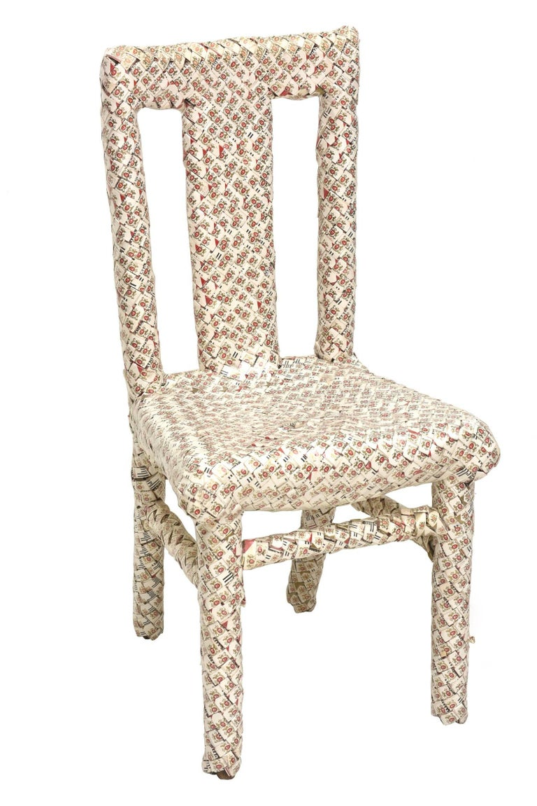 This amazing chair that is a work of art executed with over 1,000 boxes of Marlboro cigarette boxes is from the genre of prison art meets Folk Art. The boxes were folded and weaved and took years of time to make. This is all done over wood. It is by