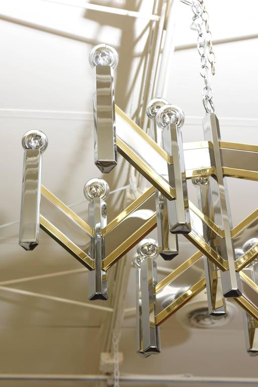 This mixed metals of brass and nickel silver of this Gaetano Sciolari for Lightolier has been professionally polished and rewired. The dramatic zig zag chevron pattern alternating nickel silver and brass houses 15 lights with special chrome tipped