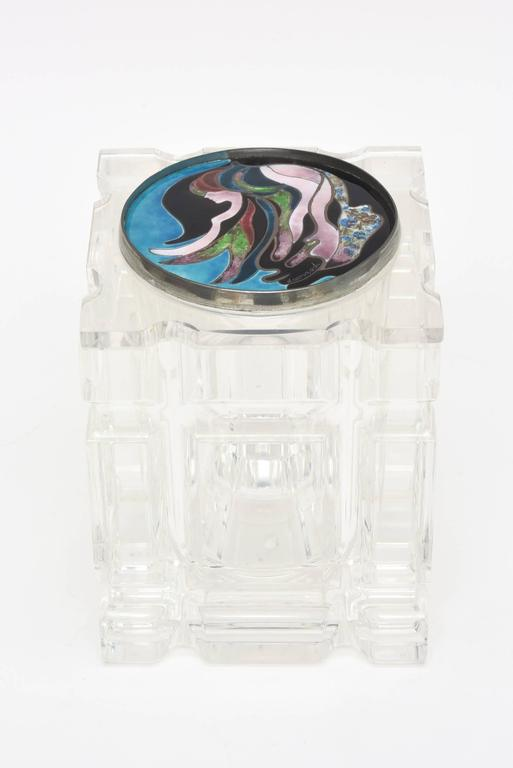 This Lucite and mixed-media box, vessel or container has a removable foiled enameled cloisonné top with a spectacular signed artistic design. The abstract top that looks like a painting is signed and reads Komard. The colors are rich in brilliant