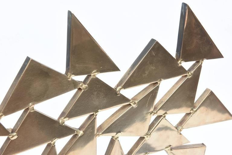 This French two-part fantastic large and arresting  solid brass sculpture has connected and welded triangles that give it dimension and movement. It has great geometric lines of triangles. It has great weight to it. It is one of a kind and from the