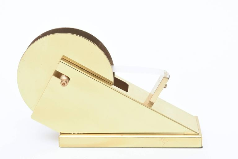 Machine Age meets modern in this vintage sleek and sculptural large brass tape dispenser and holder. It is great from all angles and a wonderful desk accessory! It even holds different widths of tape and unbolts to do so. This is a great find and