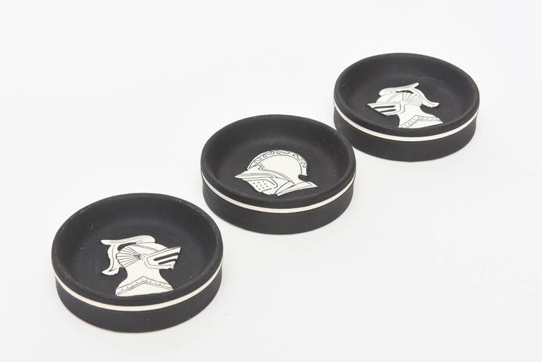 These graphic and interesting vintage German porcelain small dishes/objects are the subject matter of 3 different knights faces. The white porcelain face is raised with black drawings. The matt black porcelain bottom is outlined with white around