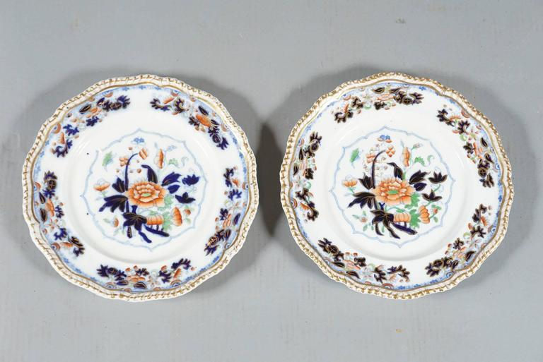 Eight English dinner plates of early Worcester Ironstone pottery in the Imari pattern, blue and red with gold scalloped rim.  The plates are beautifully hand-painted with superb rich enameling and hand gilding and signed on the back in underglaze