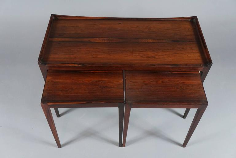"Finely crafted set of three tables having tapered legs by Danish designer, Kurt Ostervig in solid rosewood, the two square tables fitting underneath. The smaller tables measure: 14""x14""x 17""H."