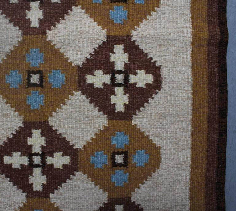 Swedish Rölakan rug in tones of brown, cream and blue. The rug designed by A Wallberg, signed AW, circa 1960s-1970s.