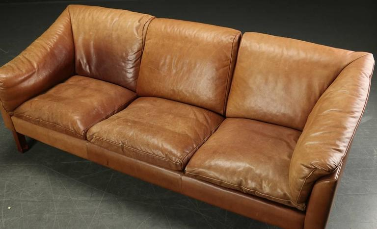 Danish modern sofa upholstered in tobacco colored leather, circa 1960s.